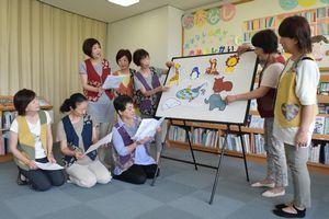 物語に登場するキャラクターをボードに張るメンバー=阿南市那賀川町苅屋の那賀川図書館