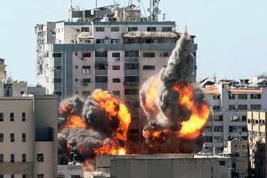 15日、パレスチナ自治区ガザでイスラエルの空爆を受け、炎と煙が上るAP通信などが入るビル(AP=共同)