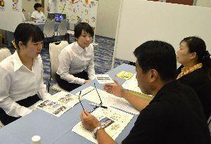 事業所職員(右側)から求人情報などの説明を受ける就職希望者=徳島市の徳島グランヴィリオホテル