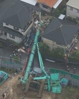 住宅に倒れた重機=23日午後1時24分、大阪府河内長野市(共同通信社ヘリから)
