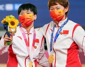 自転車女子チームスプリントで優勝し、胸元に毛沢東のバッジを着けて表彰式に参加した中国の鮑珊菊(左)と鍾天使=2日、伊豆ベロドローム