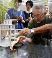 「1・17希望の灯り」の火を台湾に運ぶため「分灯」する垂水英司さん(手前)=17日午後、神戸市