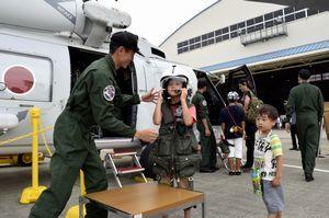 パイロットの装備品を着用する男児=小松島市の小松島航空基地