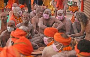 ヒンズー教の祭典「クンブ・メラ」で、ガンジス川の沐浴開始を待つマスク姿の修行僧=12日、インド・ハリドワル(AP=共同)