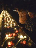 ろうそくに見入る子どもたち=小松島市立江町の立江寺