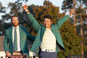 米ゴルフのマスターズ・トーナメントで、日本男子初のメジャー制覇を果たし、グリーンジャケットを着て両手を上げる松山英樹。左は前年優勝のダスティン・ジョンソン=11日、米ジョージア州のオーガスタ・ナショナルGC(ゲッティ=共同)