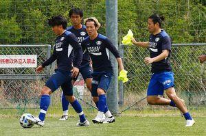 攻守の切り替えやパス回しなどのメニューをこなす岩尾(左)ら徳島の選手=18日、板野町の徳島スポーツヴィレッジ