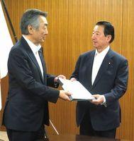 松本氏(左)から引き継ぎ書を受け取る江崎消費者行政担当相=消費者庁