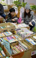チャリティーバザーで熱心に本を選ぶ親子=鳴門市立図書館