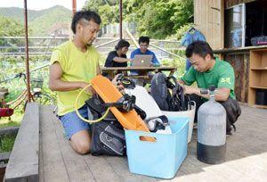 試験潜水に向けて準備を進める森永さん(左端)ら=美波町恵比須浜