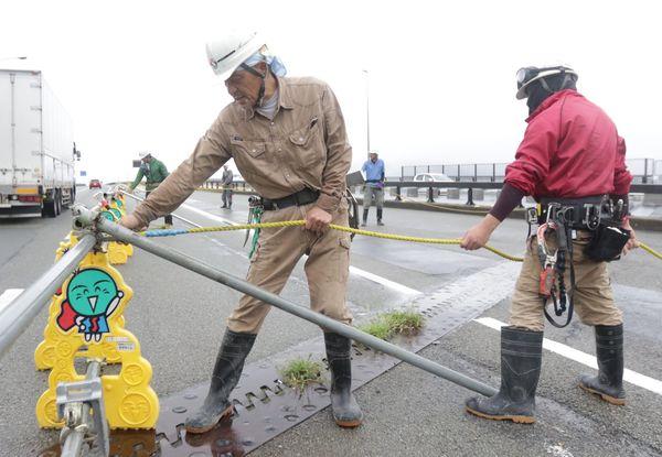 台風接近に備え、那賀川大橋の車道に設けた鉄製バリケードをロープで固定する作業員=阿南市那賀川町