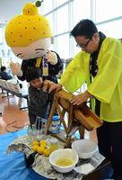 木製のユズ搾り器で搾汁の体験をする子どもら=徳島阿波おどり空港