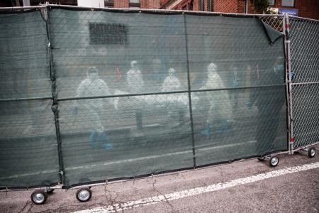 新型コロナ感染患者を運ぶ医療関係者=9日、ニューヨーク(AP=共同)