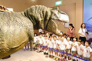 開幕したトクシマ恐竜展でティラノサウルスロボットに見入る園児たち=県立博物館