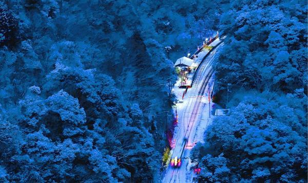 寒い朝、うっすらと雪をまとった駅を列車が駆け抜けていく=三好市池田町