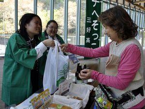 来店者(右)に商品を販売する三好高の生徒=三好市西祖谷山村今久保のかずら橋夢舞台