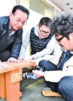 イラスト入り木製プレートをベンチに取り付けるメンバー=阿波市土成町土成