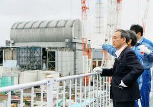 首相就任後初めての出張で福島県を訪問し、東京電力福島第1原発を視察する菅首相。奥は3号機=26日午後(代表撮影)