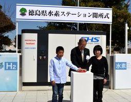 四国で初めて開設された水素ステーションの電源を入れる熊谷副知事(中)=県庁