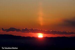 日の出時に雲の上に現れた太陽柱(サンピラー)=9日午前7時15分ごろ、阿波市土成町の西山から撮影