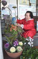 丹精込めて育てた花に、水やりをする高島さん=阿南市の宝田公民館
