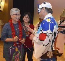踊り体験で表彰された台湾からの客(左)と阿波の風の朝田副連長(右)の会話を通訳する澤田さん=徳島市の阿波おどり会館