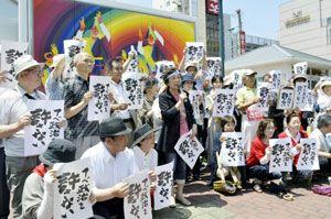 安全保障関連法案に反対の声を上げる竹内さん(中央)=徳島駅前