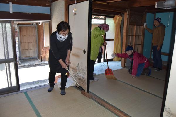 アート作品の展示会場となる民家を掃除する運営委員=牟岐町沖の出羽島