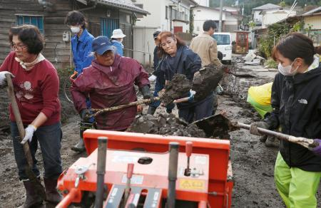 浸水被害があった家屋の泥を片付けるボランティア=23日午後、宮城県丸森町