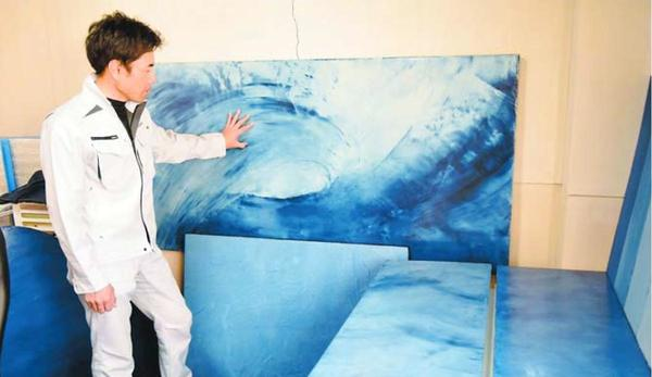 藍染風の壁板やテーブルをPRする喜田さん=徳島市秋田町2