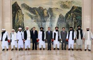 タリバンの代表団と写真に納まる中国の王毅国務委員兼外相(左から7人目)=28日、中国天津市(中国外務省のホームページより、共同)