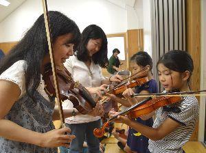 鳴門教育大の学生(左)からバイオリンの弾き方を教わる児童=徳島市の内町児童館