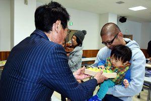 坂口町長(左)から木のおもちゃを受け取る親子=那賀町地域交流センター
