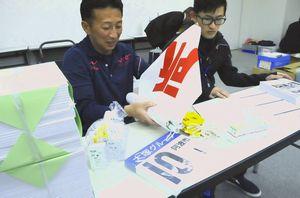 配布されたナンバーカードや旗を確認する郡市関係者=徳島新聞社