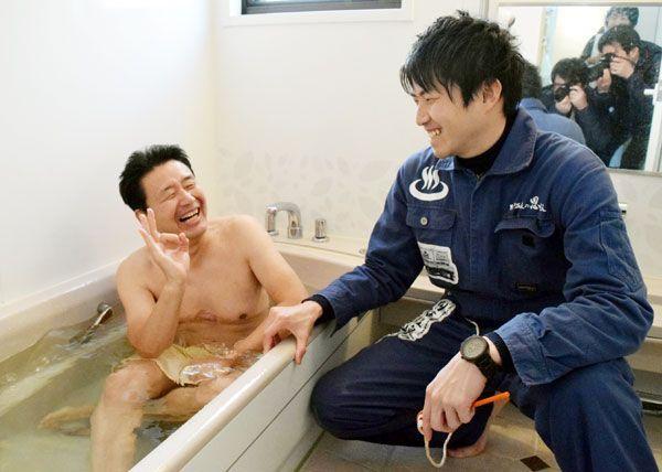 別府温泉から届けられた源泉に入る山西さん(左)と別府市職員=阿南市羽ノ浦町岩脇