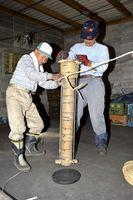 火薬を詰めた竹筒に縄を巻き付ける赤松煙火保存会の会員=美波町赤松の作業場