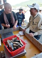 計量所で釣った魚の重量を量る参加者(右)=牟岐町牟岐浦の牟岐漁港