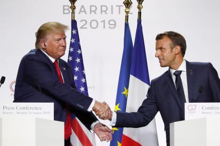 26日、G7サミット閉幕後の記者会見で握手するトランプ米大統領(左)とフランスのマクロン大統領=フランス南西部ビアリッツ(AP=共同)