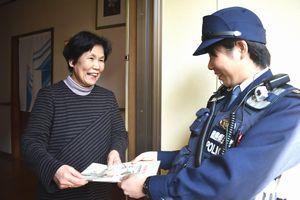 署員(右)からチラシなどを受け取る高齢者=徳島市庄町1
