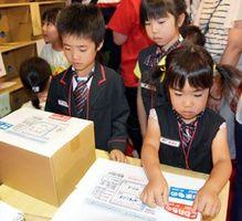 郵便局の窓口業務を体験する子どもたち=徳島市万代町の万代中央埠頭