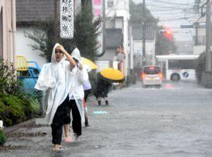 台風16号に伴う大雨で、冠水した道路を歩く人=午前11時10分、石井町石井