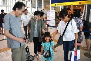 出迎えを受けて笑顔を見せる帰省客ら=徳島阿波おどり空港