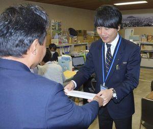 ボーナスの明細書を受け取る徳島市職員(右)=市役所