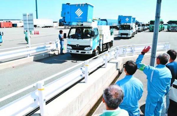関係者の見送りを受けて出発する四国電力関連会社の工事車両=徳島市東沖洲2の徳島小松島港