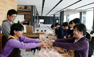 購入客に商品を手渡す施設利用者(左側)=阿南市役所