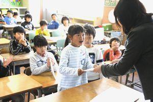 担任から通知表を受け取る児童=徳島市の城東小