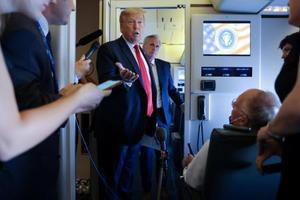大統領専用機内で記者団に話すトランプ米大統領(ロイター=共同)