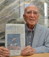 コウノトリのひなの成長を伝える徳島新聞を手に、作詞への思いを語る木村さん=徳島市佐古五番町