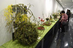 手の込んだフラワーデザイン作品に見入る来場者=徳島市シビックセンター