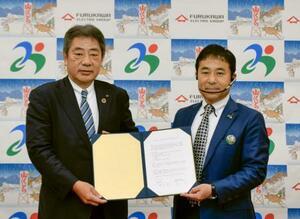 島根県美郷町で古河電気工業との協定書を見せる嘉戸隆町長(右)=24日午後